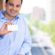 Closeup portrait of handsome man holding blank business card isolated on a city background with trees, buildings, roads, and cars — Stock Photo