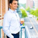 Man enjoying drink on balcony — Stock Photo #29653051