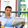 Happy man enjoying his paper and eating breakfast at home — Stock Photo