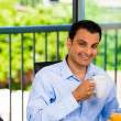 Happy, successful businessman enjoying cup of coffee or tea inside his home or office — Stock Photo