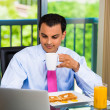 Portrait of handsome businessman or student eating breakfast and happily typing and working on his laptop — Stock Photo