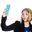 Portrait of a cute blonde woman taking photo of herself with a smart phone — ストック写真