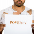 A close-up portrait of a homeless, hopeless hungry man holding a sign which says poverty — Stock Photo