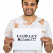 A close-up portrait of a homeless man previously a healthcare worker holding a sign which says - health care reform — Foto Stock