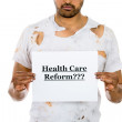 Foto Stock: Close-up portrait of homeless mpreviously healthcare worker holding sign which says - health care reform