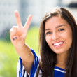A close-up picture of a beautiful happy woman giving a victory sign relaxing on a summer day on a balcony of a new apartment — Stock Photo