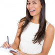 A close-up portrait of a beautiful laughing secretary or student, businesswoman holding a clipboard and a pen — Stock Photo