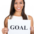 A portrait of a beautiful smiling, happy businesswoman holding a sign which says goal — Stock Photo
