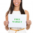 A portrait of a beautiful smiling female holding a sign which says free market. — Stock Photo