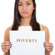 Close-up portrait of a beautiful sad woman holding a sign which says poverty — Stock Photo #29695349