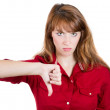 Unhappy woman giving thumbs down gesture looking with negative expression and disapproval. — 图库照片