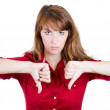 Unhappy woman giving thumbs down gesture looking with negative expression and disapproval. — Stockfoto