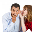 Young attractive girl whispering to a young man a secret, he is shocked — Foto de Stock
