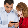 A close-up portrait of a young woman and man looking shocked with opened mouth on a cell phone reading an sms, e-mail or viewing latest news — Stock Photo