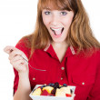 Portrait of a pretty young happy redhead woman eating fruit salad  — Foto de Stock
