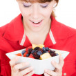 A close-up, cropped portrait of a beautiful woman holding a bowl with fruit salad — Stok fotoğraf