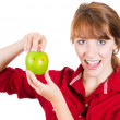 A close-up portrait of a beautiful young smiling woman holding a fun apple — Stok fotoğraf