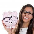 A close-up portrait of a young attractive smiling woman wearing glasses and holding a piggy bank, isolated on a white background. Eye wear sale. — Stock Photo