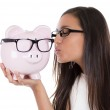 Glasses sale concept. Happy woman kissing piggy bank wearing eyewear glasses. Mixed race female model isolated on white background. — Stock Photo