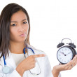 A close-up portrait of a young female doctor, nurse holding an alarm clock, very unhappy pressured by time, isolated on a white background. — Stockfoto