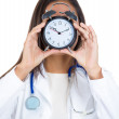 A close-up portrait of a female doctor holding alarm clock in front of her face, isolated on a white background. Busy physicians daily schedule. — Stock Photo