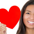 A close-up cropped image of a smiling young woman holding a heart, isolated on a white background — Stock Photo #29695915