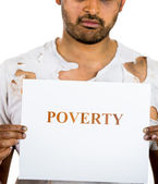A close-up portrait of a homeless, hopeless hungry man holding a sign which says poverty — Foto de Stock