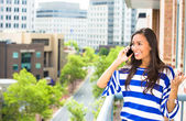 A portrait of a beautiful woman talking on a cell phone relaxed on a balcony of her apartment on a city background — Stock Photo