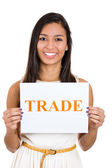 A portrait of a beautiful smiling female holding a sign which says: trade — Stock Photo