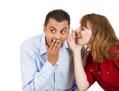 Young attractive girl whispering to a young man a secret, he is shocked — Stock Photo
