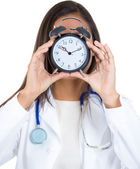 A close-up portrait of a female doctor holding alarm clock in front of her face, isolated on a white background. Busy physicians daily schedule. — Stok fotoğraf