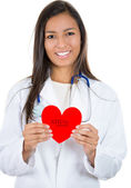 A close-up portrait of a smiling, friendly female doctor holding a heart, isolated on a white background. Cardiology care. — Stock Photo