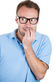 Nerdy guy with glasses biting his nails — Stockfoto
