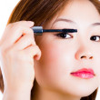 Close up of woman face with mascara brush — Stock Photo