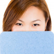 A female student hiding face behind clipboard — Stock Photo