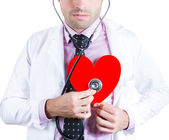 Portrait of a friendly male doctor listening to a heart — Stock Photo