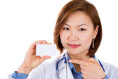 A female doctor pointing on a blank business card — Stock Photo
