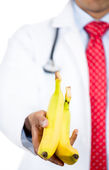 Doctor showing two bananas — Foto Stock
