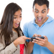Woman and man looking shocked on a cell phone reading an sms — Stock Photo