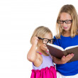 Sisters with glasses sharing and reading a book — Stok fotoğraf