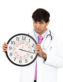Doctor holding up big clock — Stock fotografie