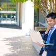 Stock Photo: Handsome businessmin suit working on laptop on sunny day