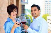 Man and woman toasting wine on outside balcony — Stock Photo
