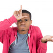 Stockfoto: Mdisplaying loser sign on his forehead