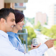 Man and woman drinking wine on outside balcony — Stock Photo