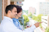 Man and woman drinking wine on outside balcony — Stok fotoğraf