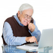 Mature man biting finger nails trying to type on laptop — Stock Photo