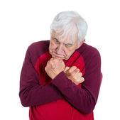 Mature man holding his arms close to chest — Stock Photo