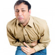 Closeup portrait of handsome, miserable, upset, young guy, doubling over in stomach pain, looking very sick — Stock Photo