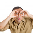 A closeup studio portrait of a young handsome, serious man looking through his fingers like binoculars — Stock Photo